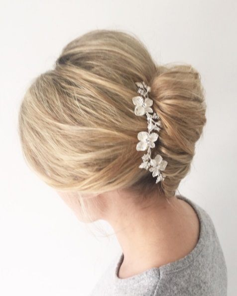 Wedding updos for long hair: Side shot of a woman with long blonde hair styled into a French twist, complete with a floral hair accessory.