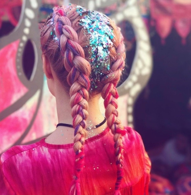 backshot of model at glastonbury with boxer braids and glitter