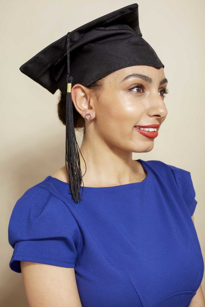 amra with her natural hair in a low bun wearing a graduation cap and blue short sleeve dress