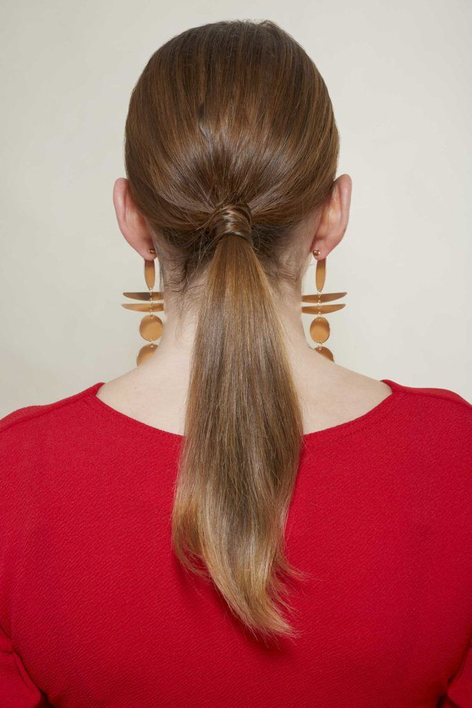 back view of leona with her brown hair in a low wrapped ponytail wearing a red dress with gold geometric earrings