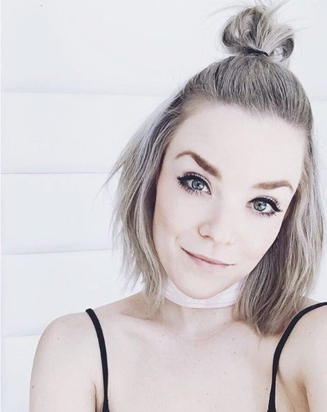 woman with short bob length icy ash blonde hair in a half up top knot