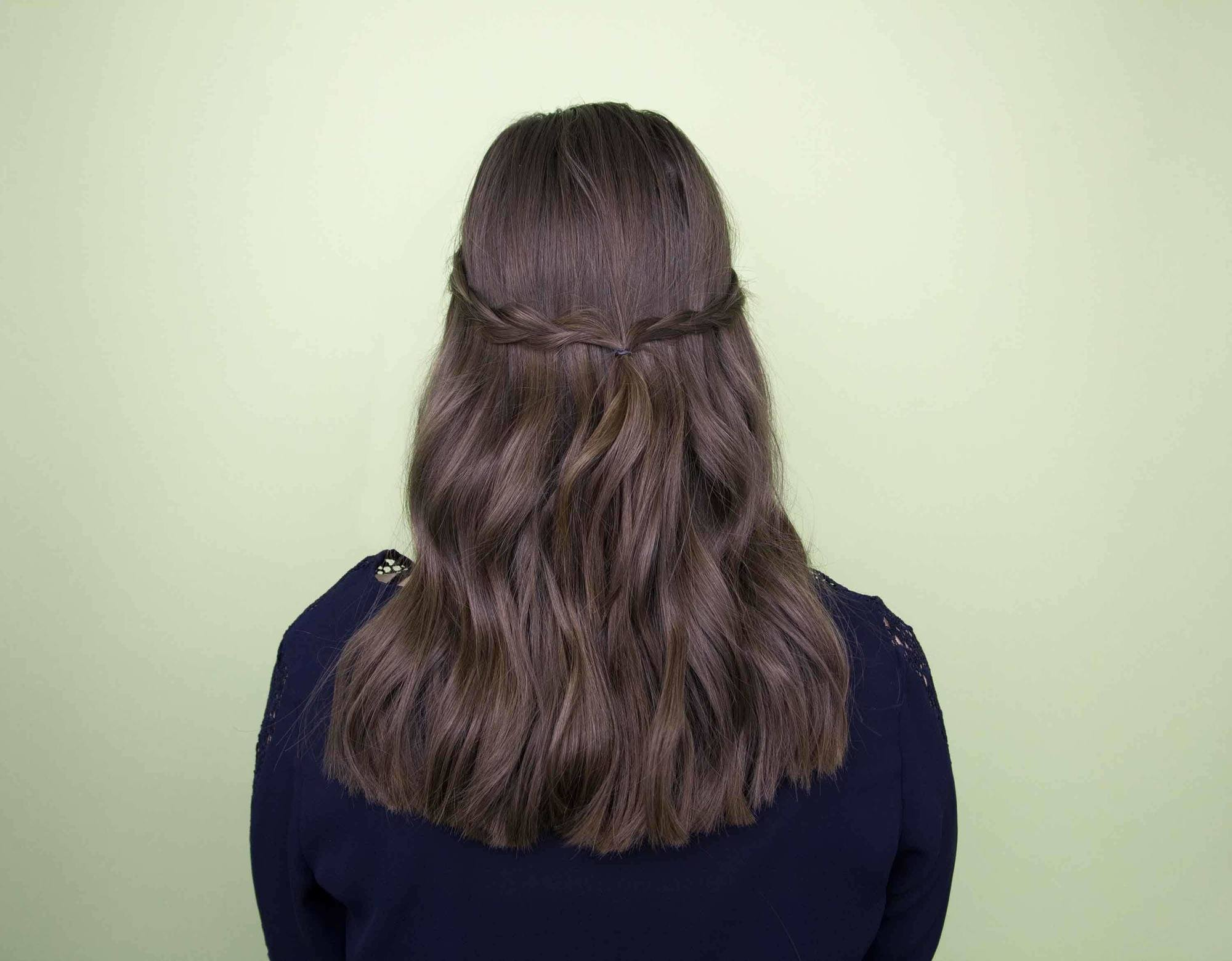 Festival hair: back view of brunette woman with medium length hair styled with single braids pinned at the back in studio setting