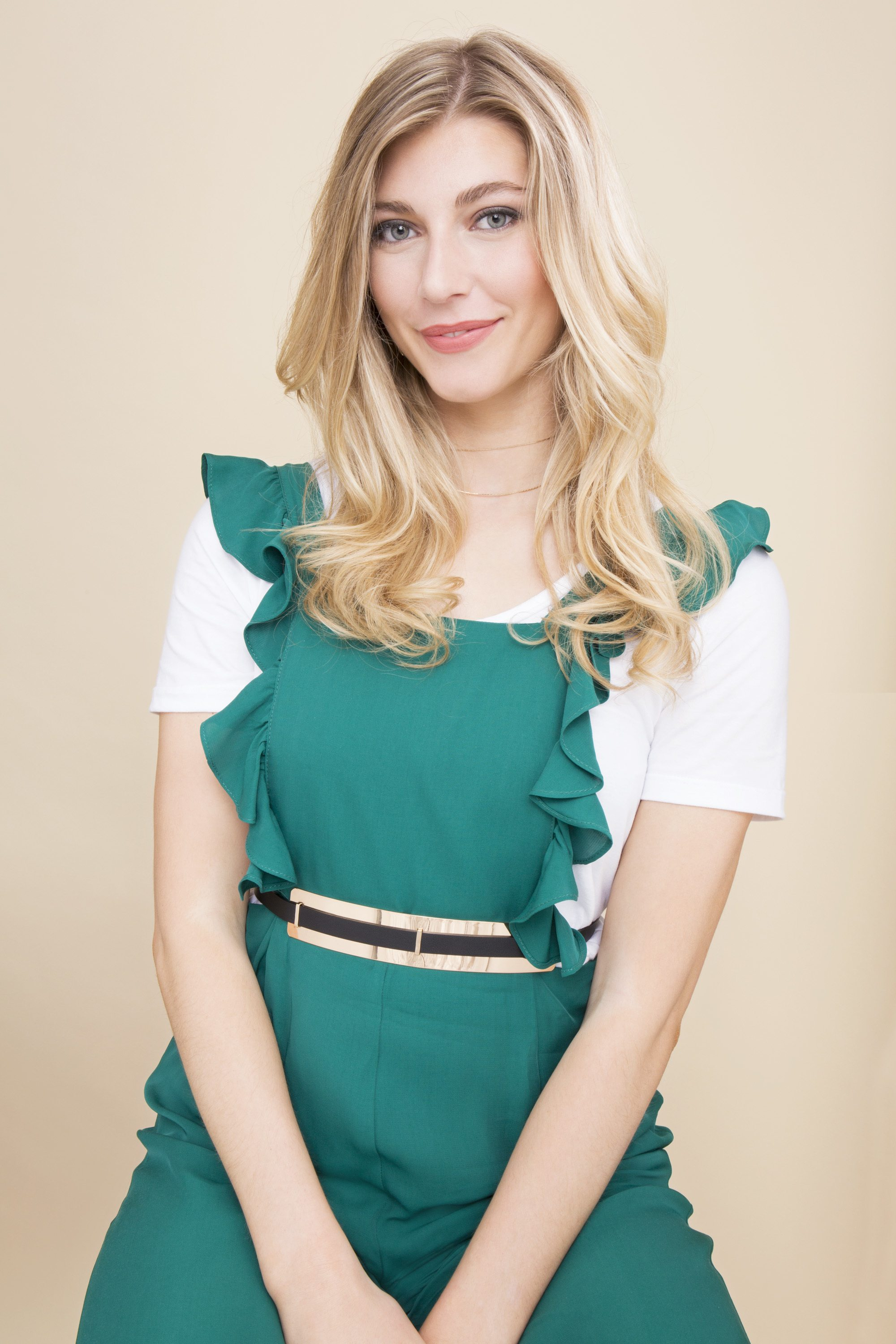 blonde woman with soft curls in a green dress