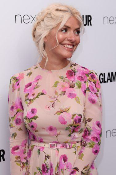 holly willoughby wearing a floral dress at the glamour woman of the year awards with her blonde hair in a braided updo