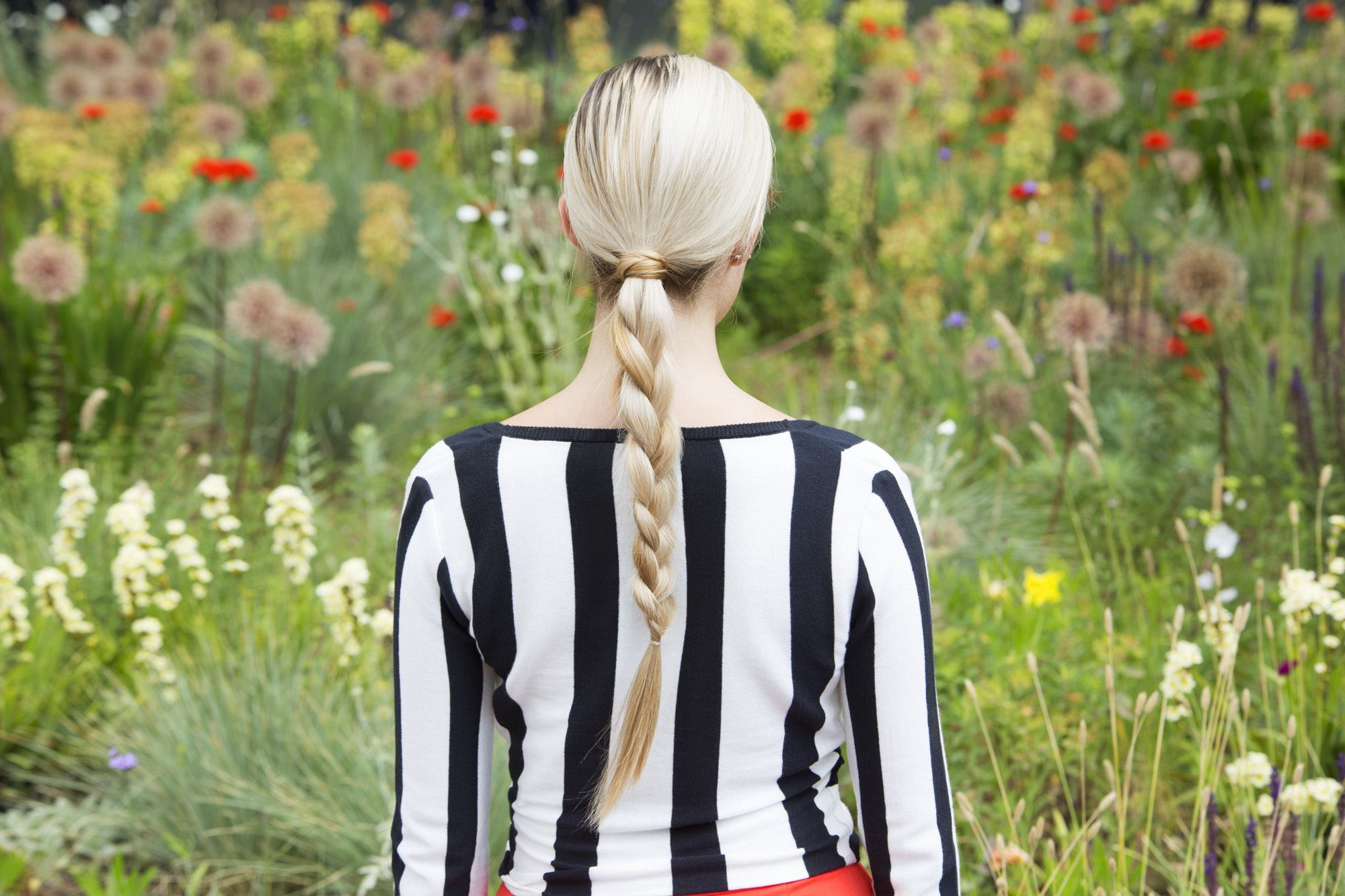 blonde model wearing a black and white striped top with her hair in a low braided ponytail