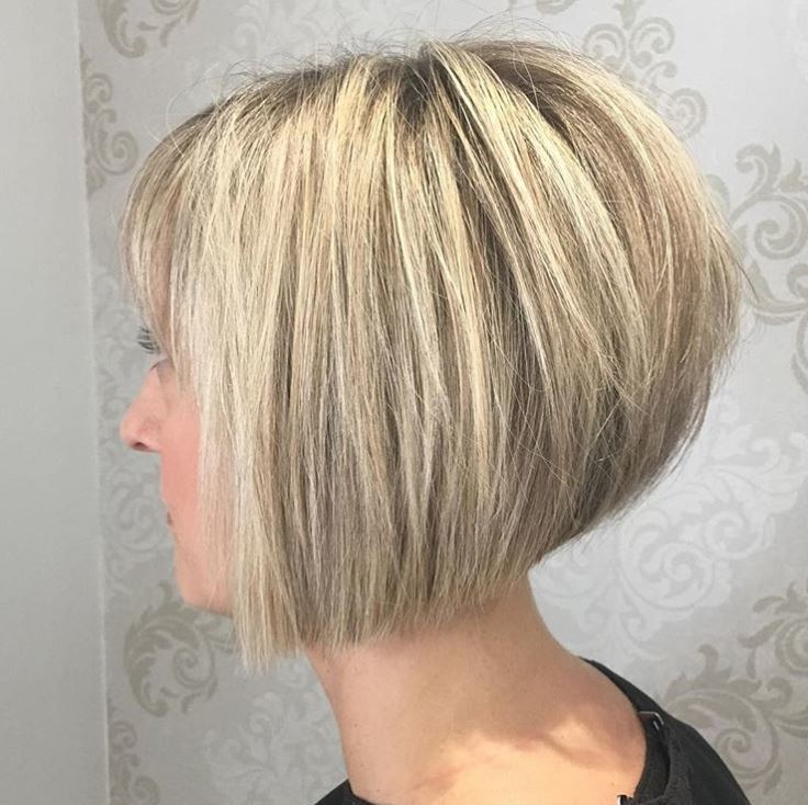 side view of woman with blonde highlighted hair styled in a graduated choppy bob