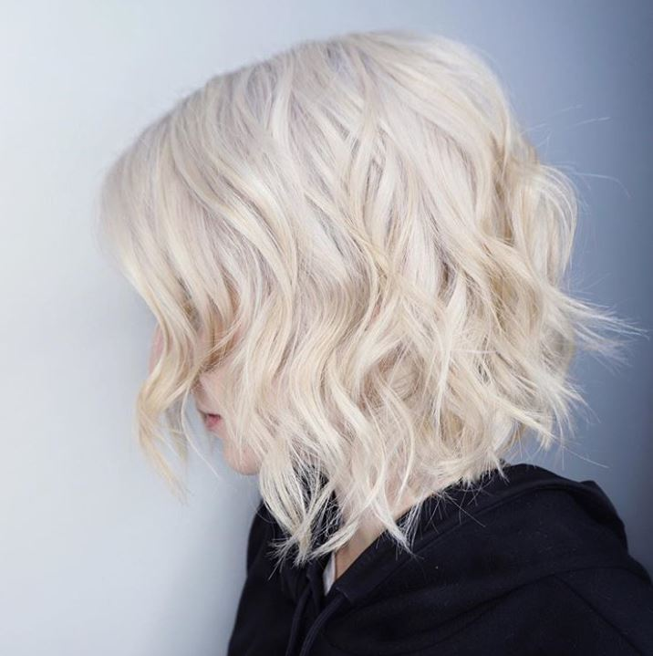 side view of a woman with a wavy platinum choppy bob