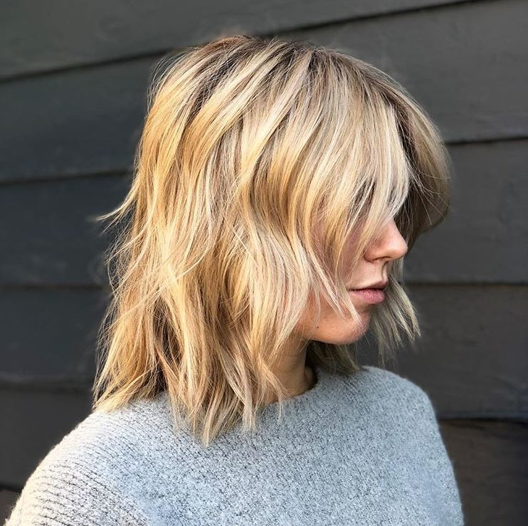 side view of woman with blonde highlighted short choppy bob shag haircut