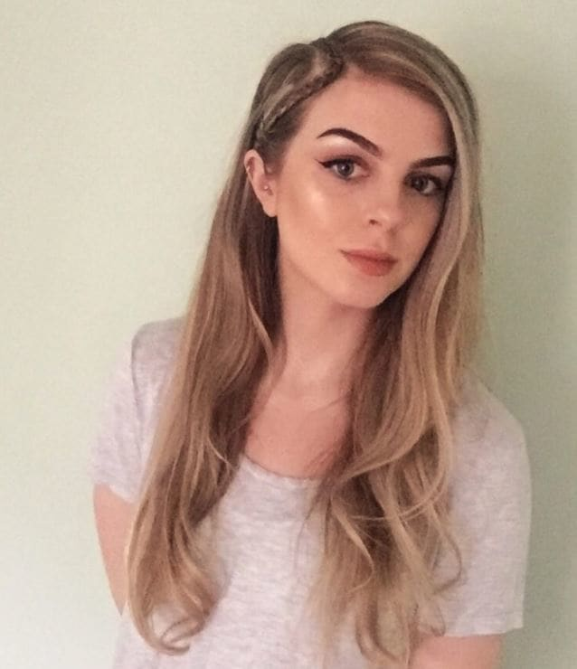Long dirty blonde hair in side parting with single braid on the side.