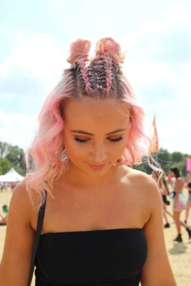 Lovebox 2018 festival hair: woman at festival with pink wavy medium length hair styled with two dutch braids down the centre going into mini buns with glitter down her roots