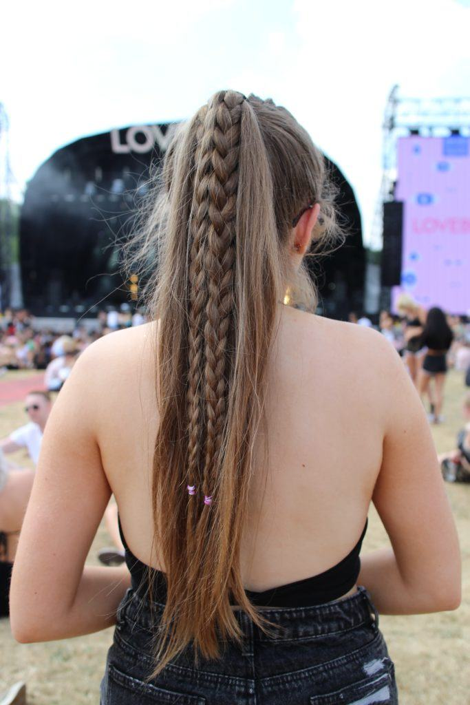 Lovebox 2018 festival hair: back view of girl with very long light brown straight hair in high ponytail with hidden braids through the length of the hair wearing a backless black top