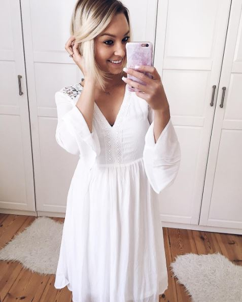 A blonde with natural looking ombre and an angle bob (pob) wearing a white dress taking a selfie