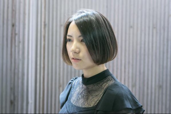 A brunette Asian woman with a shiny posh bob hairstyle