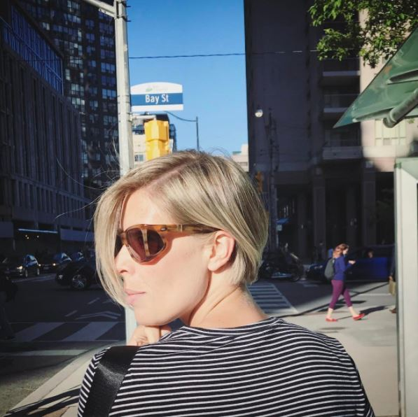 Blonde woman wearing sunglasses with a posh bob parted to the side