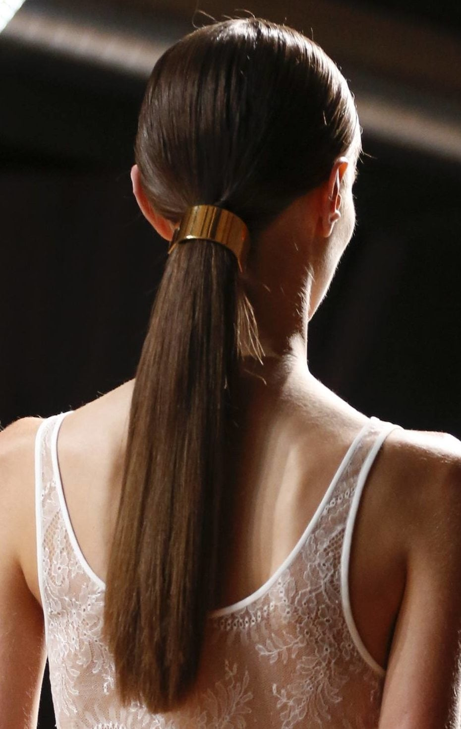 brunette model in a white lace dress with her hair in a high ponytail with wrap accessory