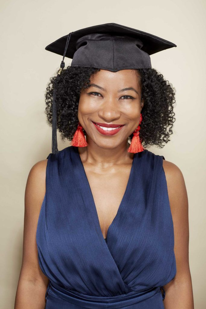 jeanette with twist out hair wearing a graduation cap, navy dress and orange tassel earrings