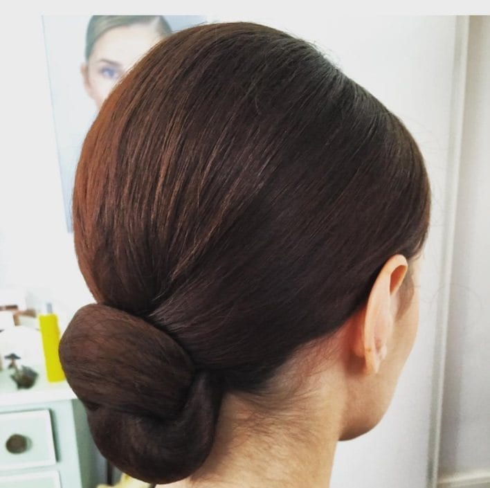 mother of the bride hairstyles for long hair: woman with low volumised ballerina bun hairstyle