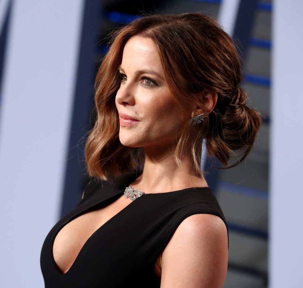 hairstyles for wavy hair: kate beckinsale on red carpet with dark golden brown wavy hair styled in a low undone bun