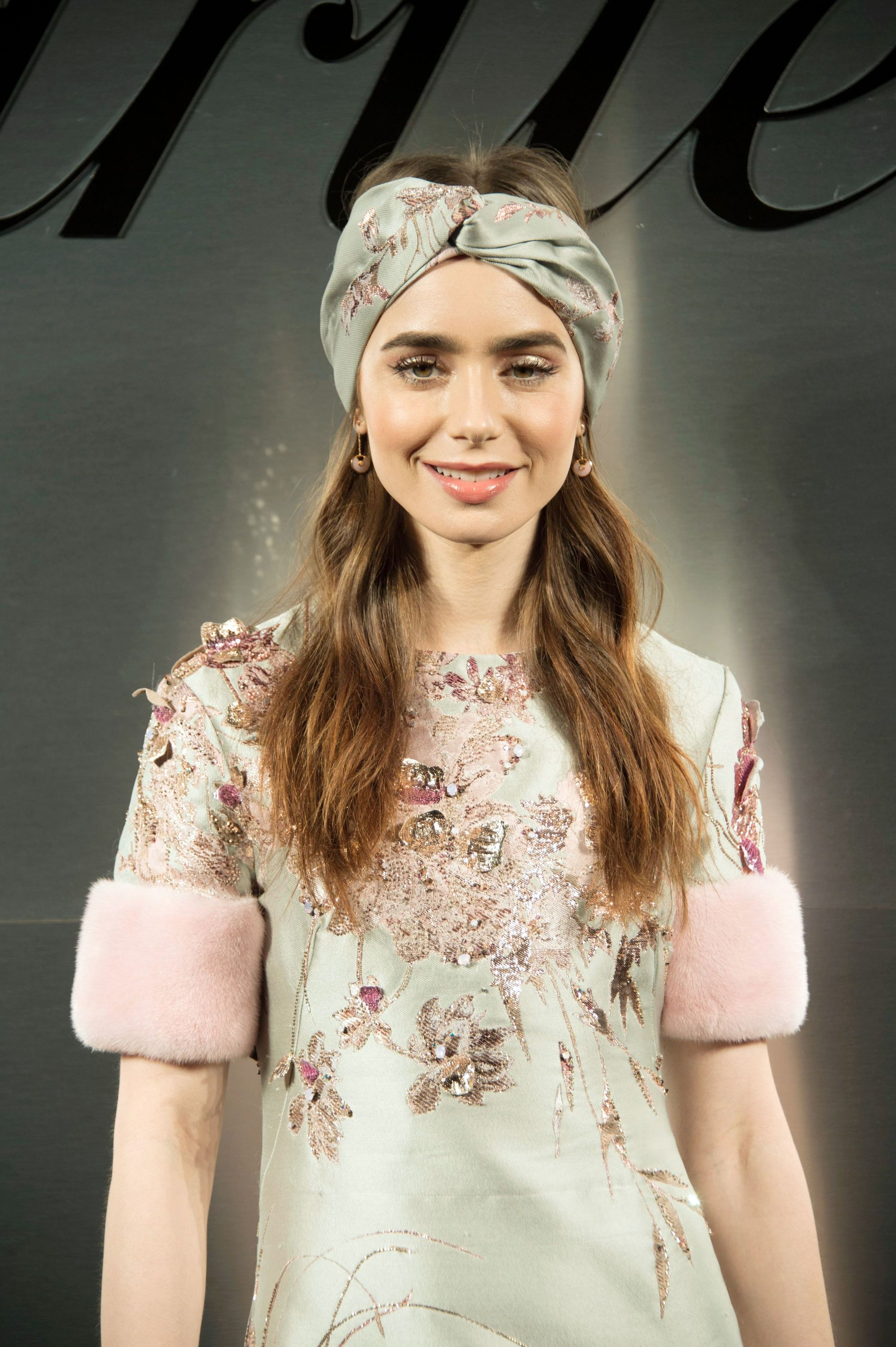 Lily Collins long wavy light brown hair with turban style headband at red carpet industry event.