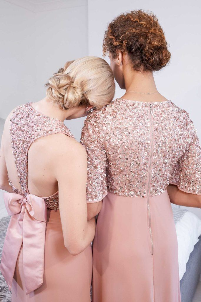 updos for wedding: close up shot of two models with low knotted bun, wearing pink gowns and posing in a bedroom