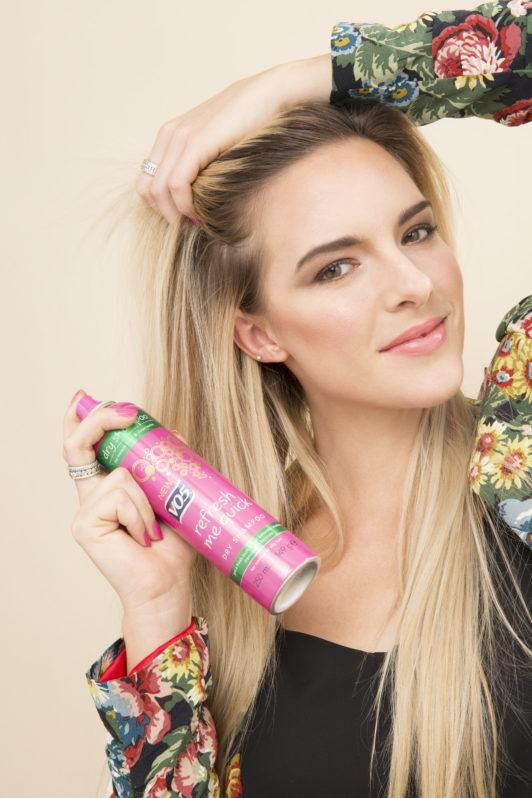 blonde model spraying vo5 dry shampoo into her roots