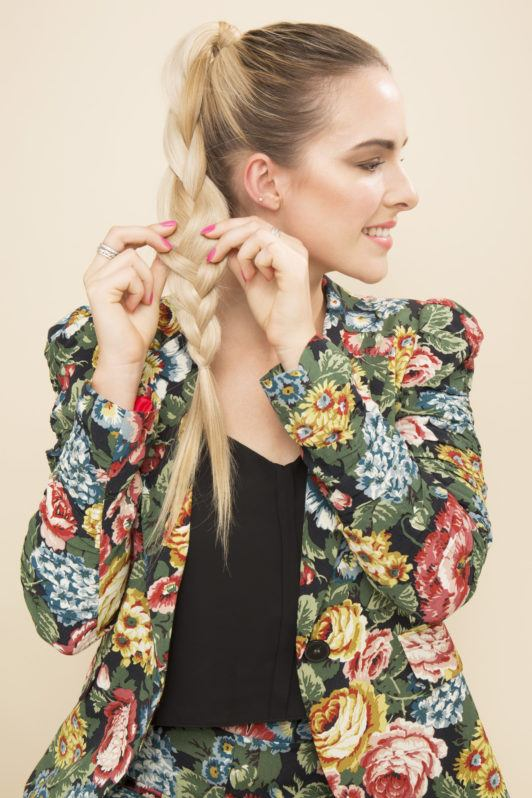 blonde model pulling apart her ponytail braid to make it bigger