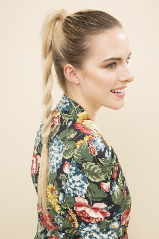 blonde model wearing a floral blazer with her hair in a high braided ponytail hairstyle