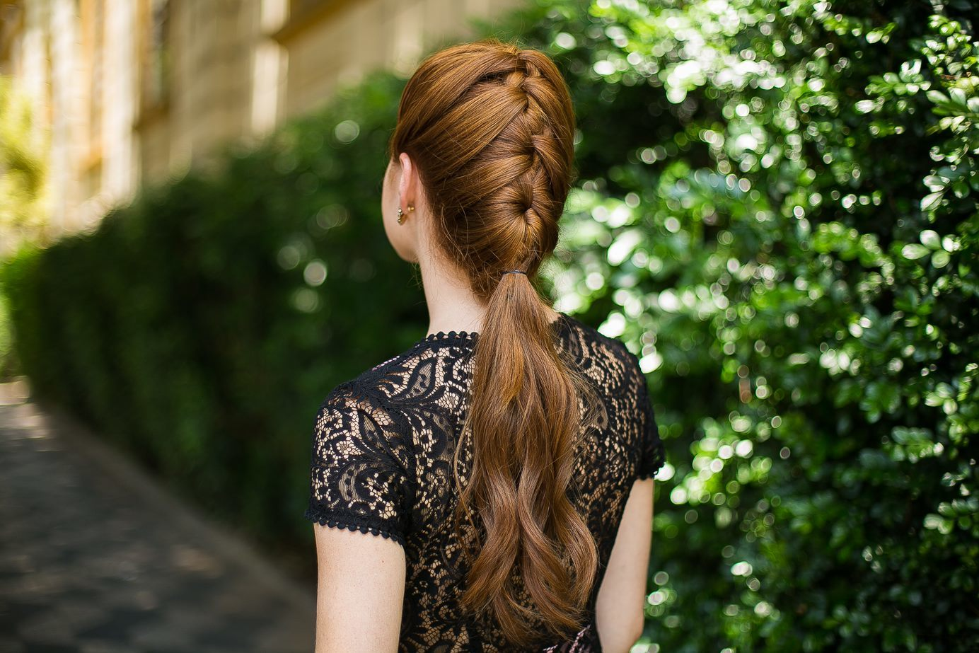 Wedding updos for long hair: Back shot of a model with long dark ginger hair styled into a French braided ponytail, wearing a dark dress and posing outside.