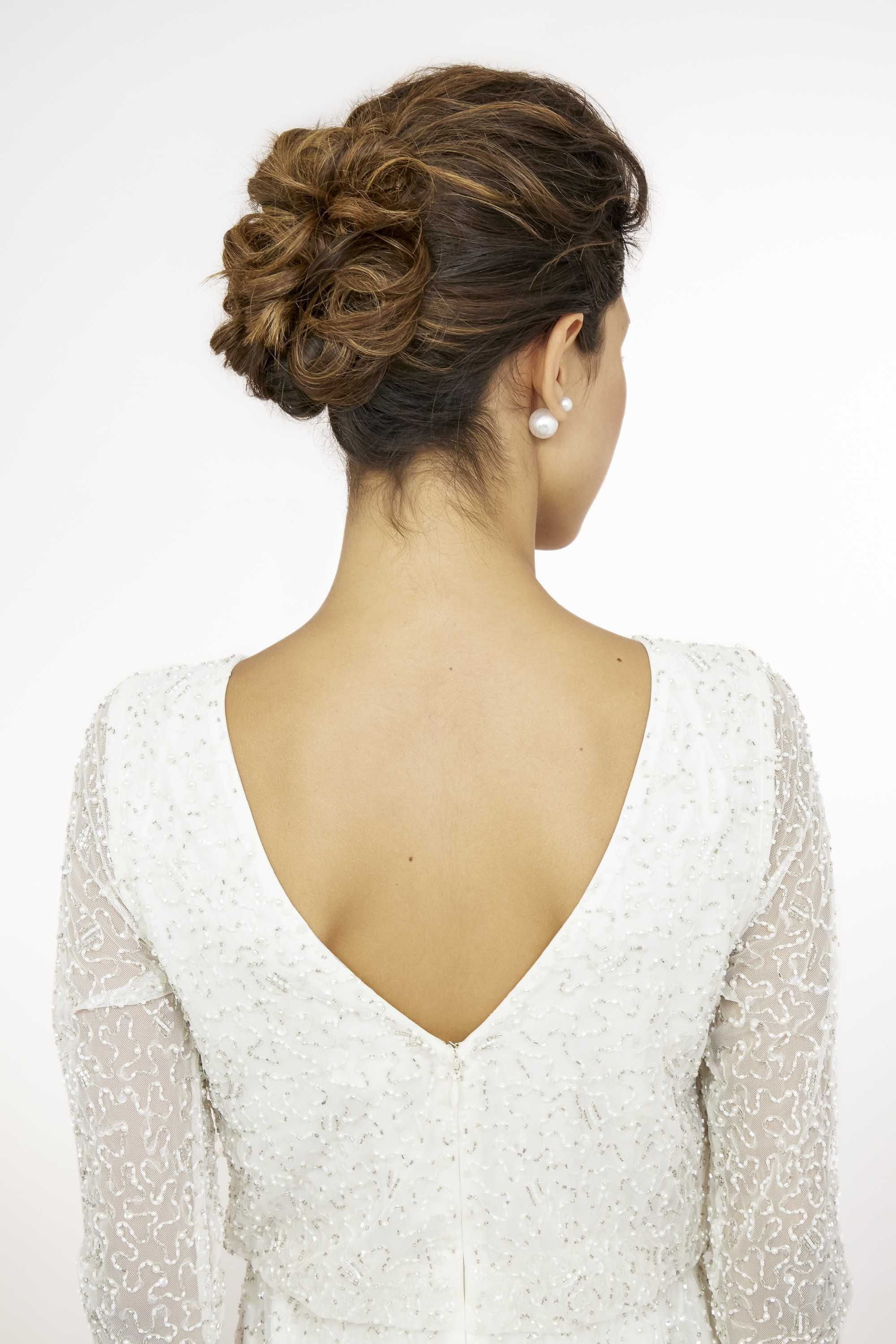 wedding updos: close up shot of model with wavy bridal updo, wearing white dress and posing in a studio