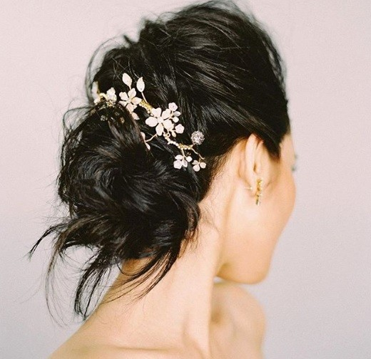 Wedding updos for long hair: Side shot of a woman long brown hair styled into a textured bun, complete with a barrette hair accessory.