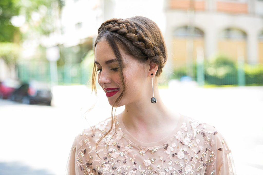 Wedding updos for long hair: Close up shot of a model with long medium brown hair styled into a milkmaid braid updo, wearing pink glittery top and posing outside.