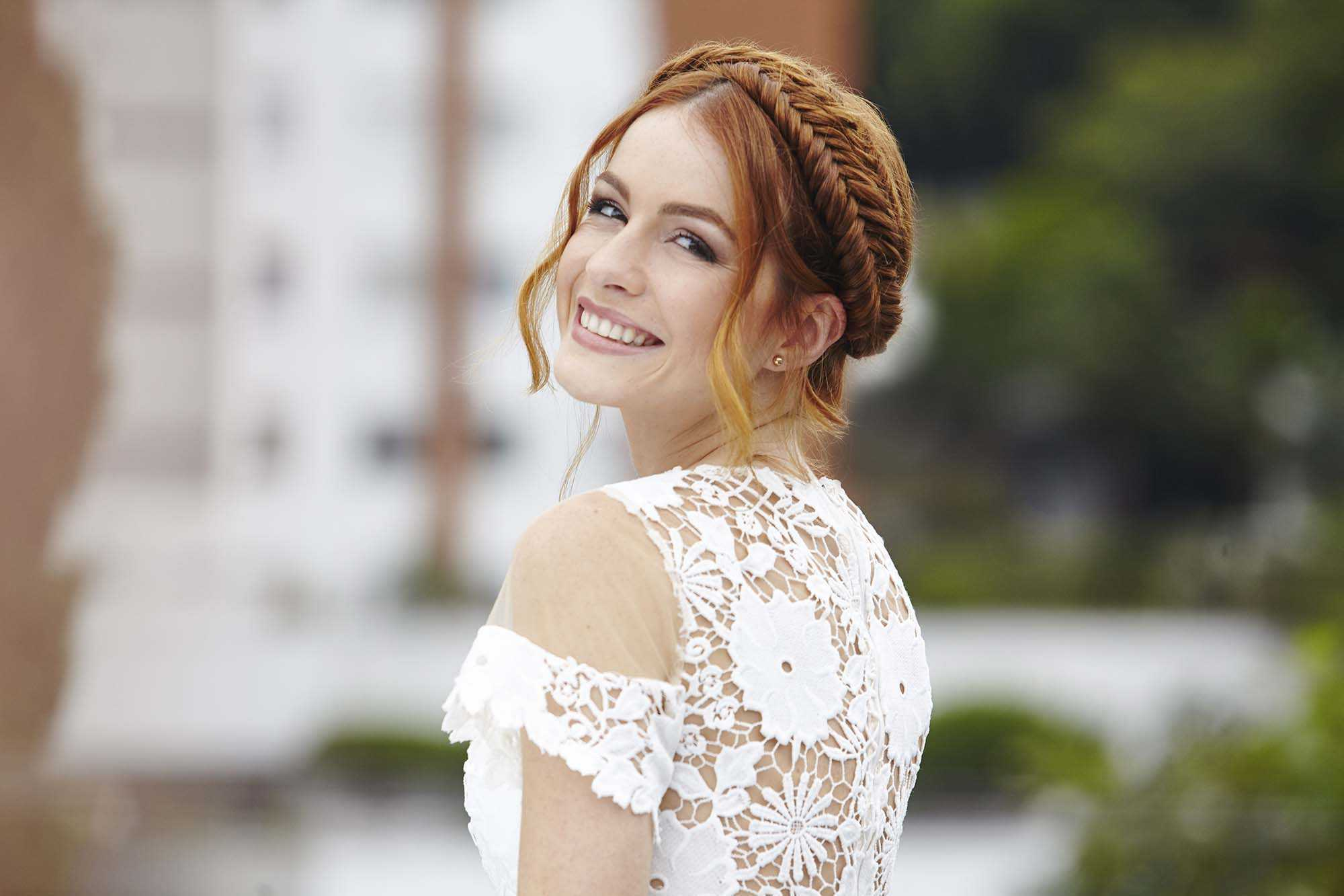 wedding hair updo: close up shot of woman with messy fishtail braid, wearing floral wedding dress