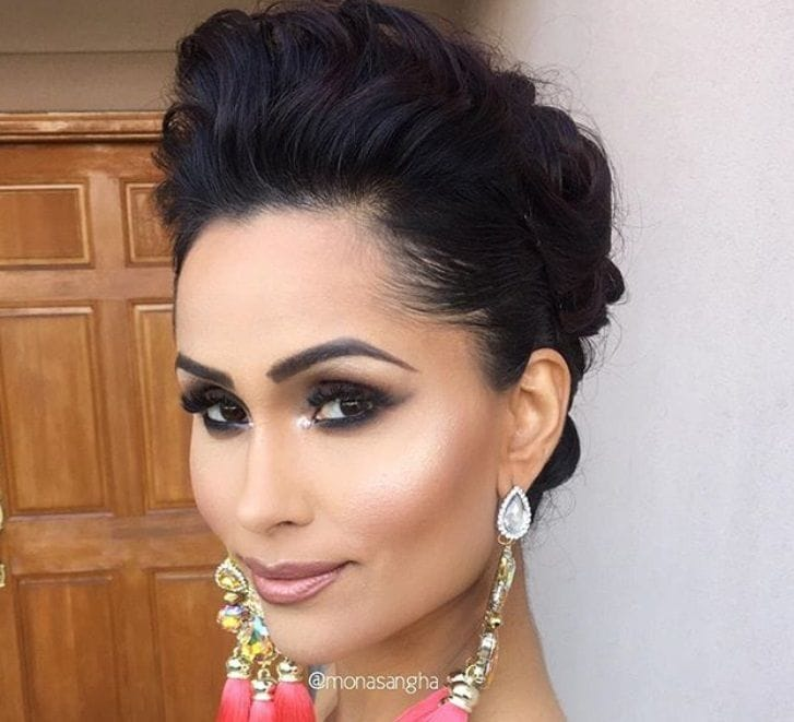 Indian wedding hairstyles: close up shot of bride with dark hair styled into a wavy coiffed updo, wearing drop earrings and posing in a bedroom setting