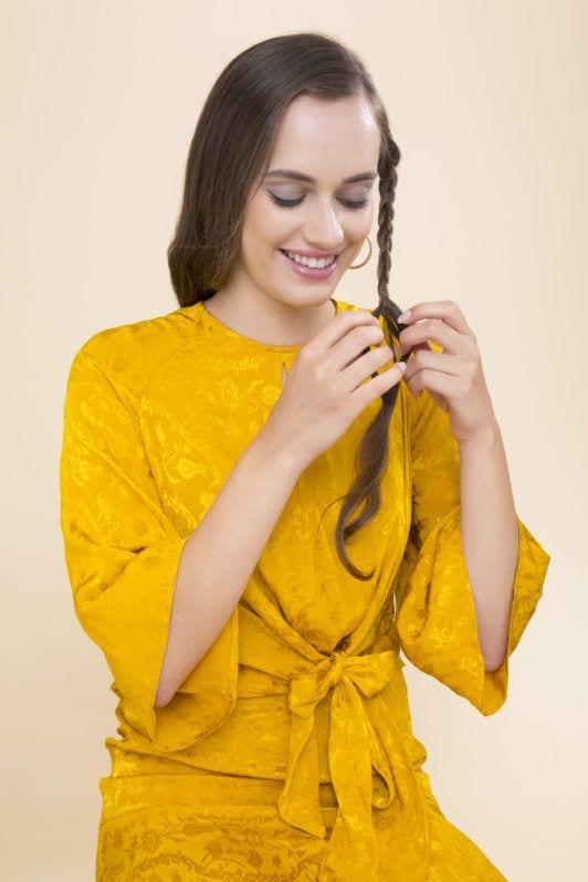 Overnight curls tutorial: medium brown hair model with long straight hair unravelling her braid