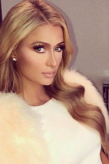 paris hilton with long blonde blow out hairstyle wearing white dress
