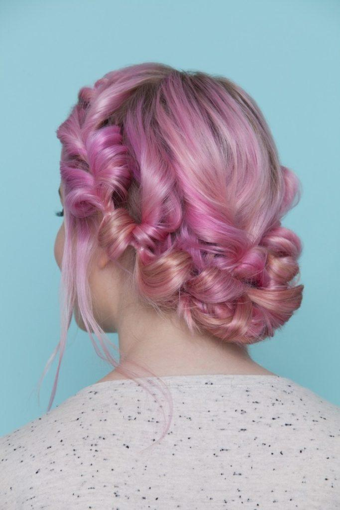 Festival hair: back view of woman with candyfloss pink hair styled ina pull through crown hairstyle sitting against a blue studio backdrop