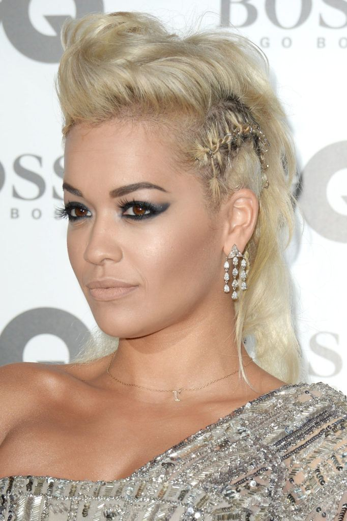 Rita Ora wears blonde hair in mohawk style with hair rings in side braids