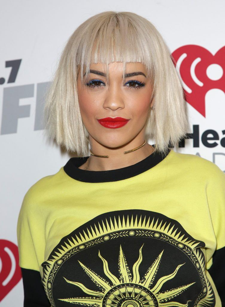 rita ora with a straight platinum choppy bob with bangs with bold red lipstick