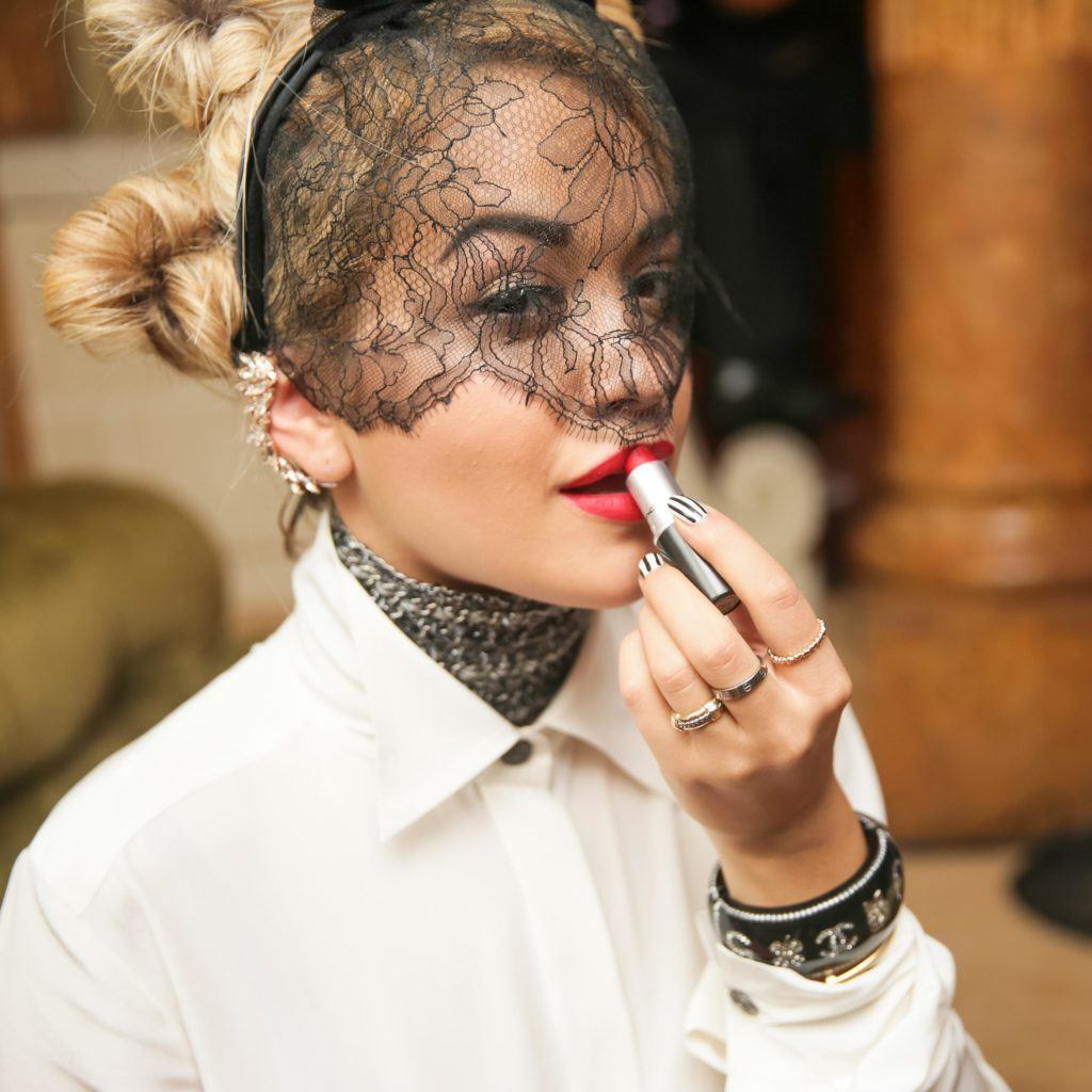 Singer Rita Ora with blonde hair in bun updos wearing a black new veil headband, looking at the camera while applying red lipstick