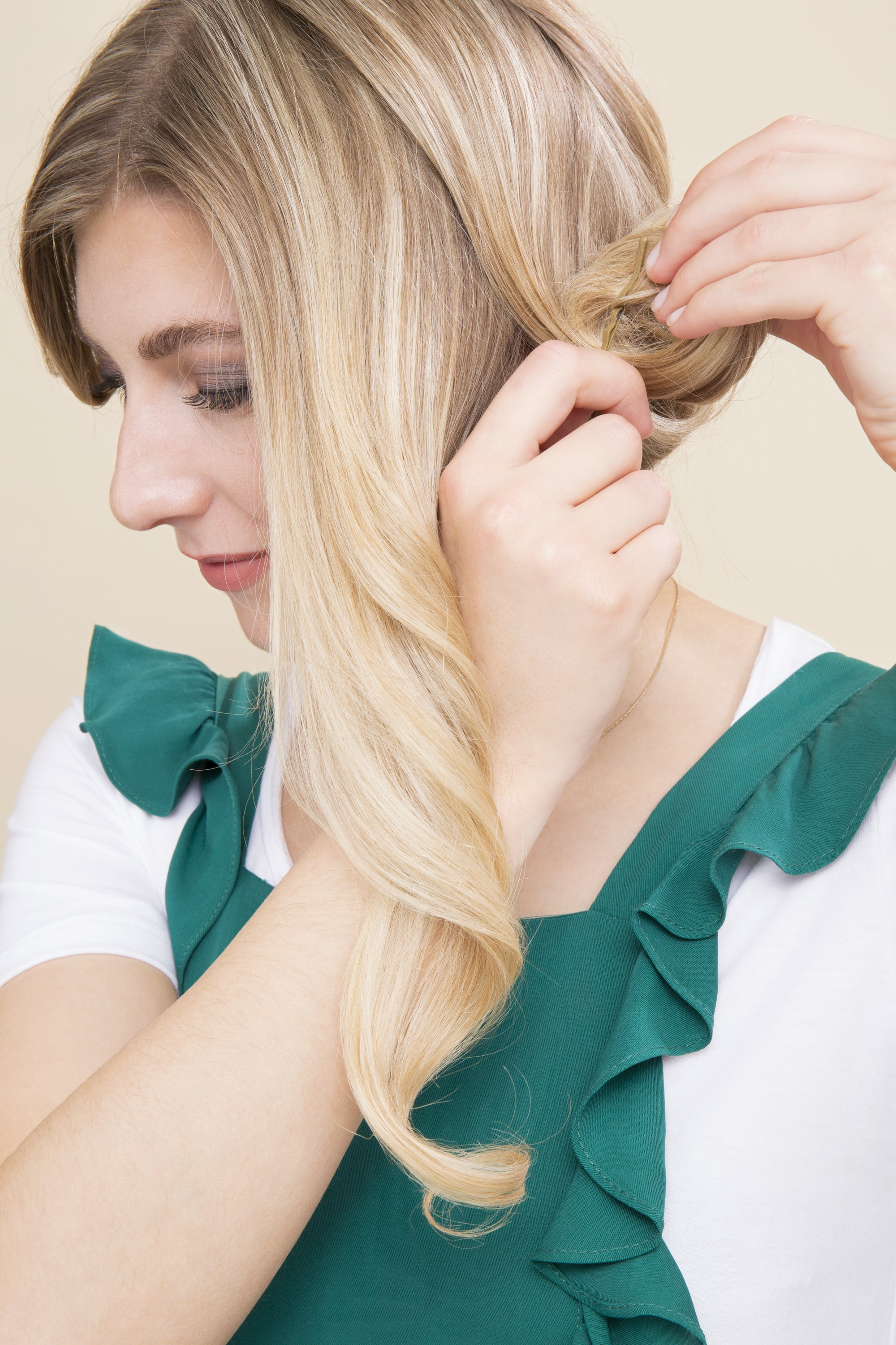 blonde woman rolling her hair into a pin curl