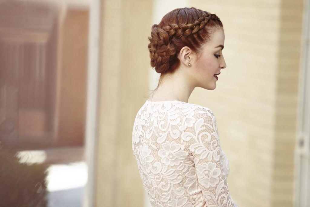 Wedding updos for long hair: Side shot of a model with long dark red hair styled into rose braided bun, wearing a white lace dress and posing outside.