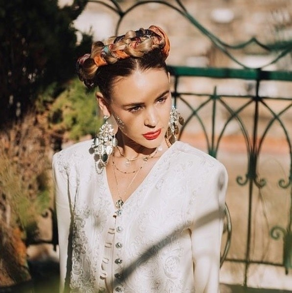 Boho hairstyles: Outdoor shot of a brunette woman with her hair in a Frida Kahlo style braided updo with patterned scarf
