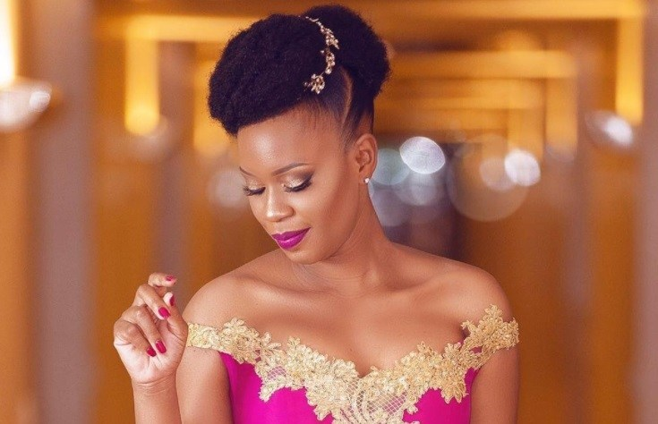 mother of the bride hairstyles for short hair: black woman with short afro fauxhawk hairstyle with gold hair accessory wearing pink