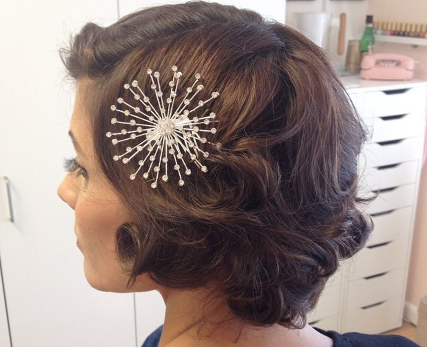 mother of the bride hairstyles for short hair: woman with short curled vintage hair wearing a silver hair accessory