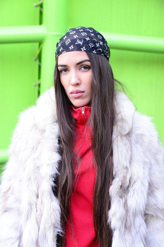 Street style picture of a woman with long straight brown hair wearing a Louis Vuitton logo print bandana standing against a green backdrop.