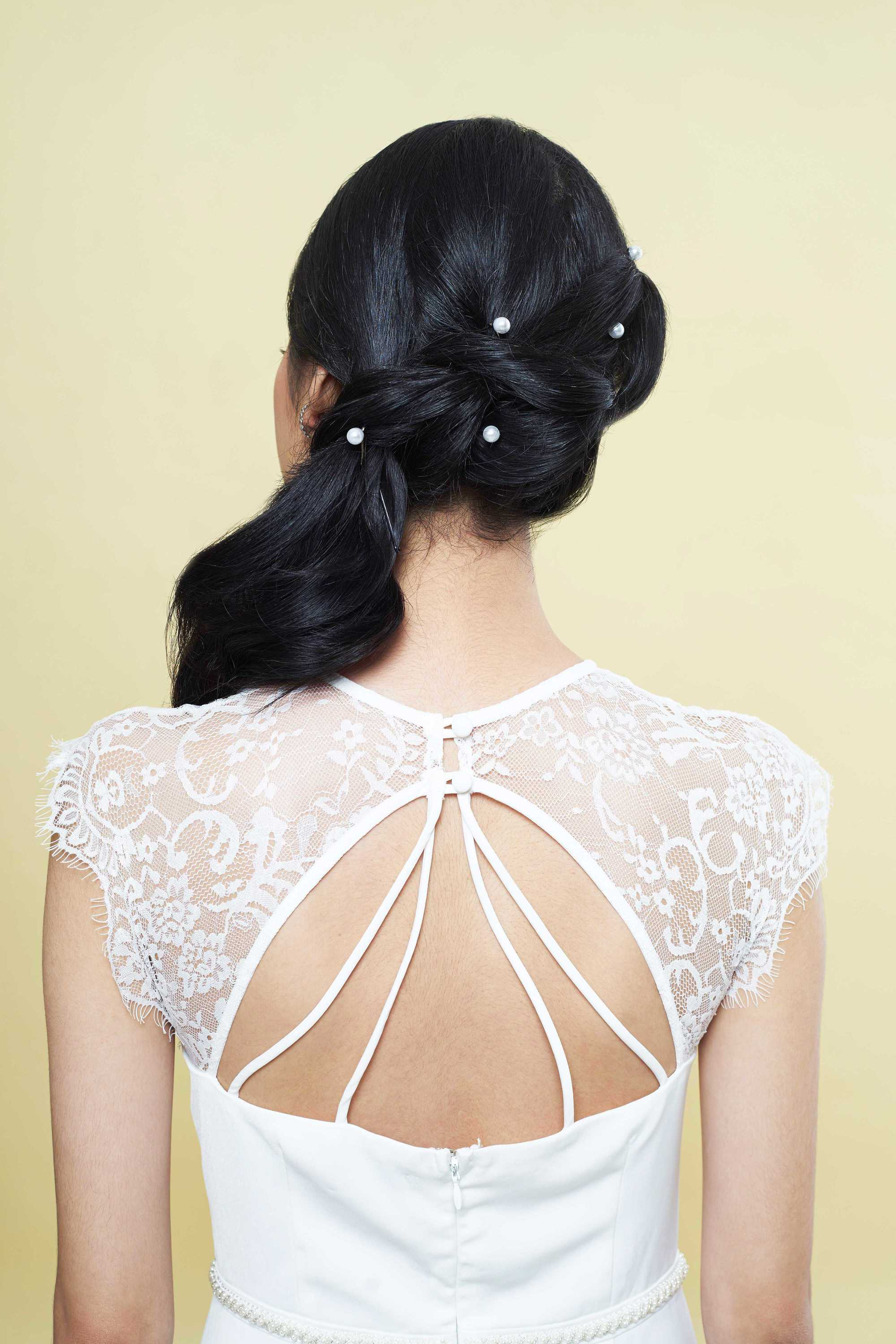 Wedding updos for long hair: Back shot of a bride with long dark hair styled into twisted ponytail, complete with pearl hair accessories, wearing a white lace dress and posing in a studio.