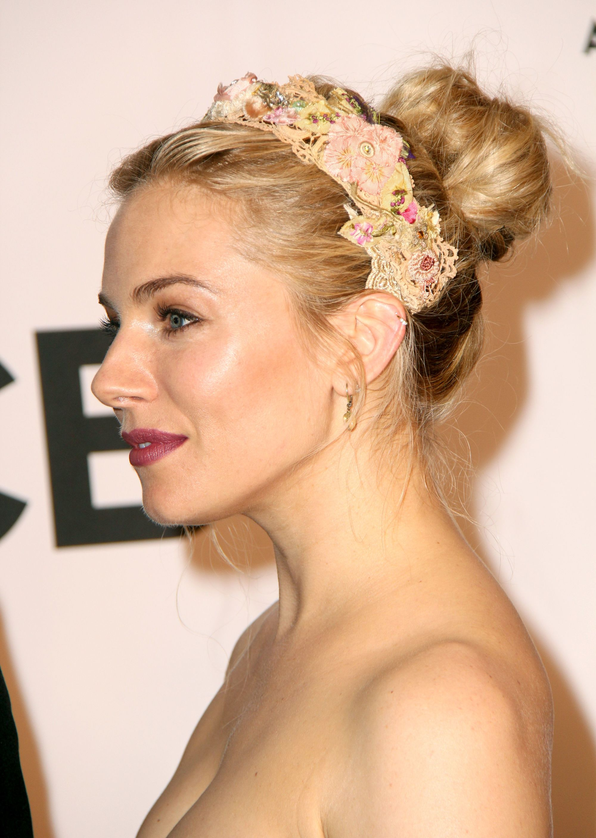 Side view of Sienna Miller on the red carpet with her blonde hair styled in a bun with a peach coloured headband