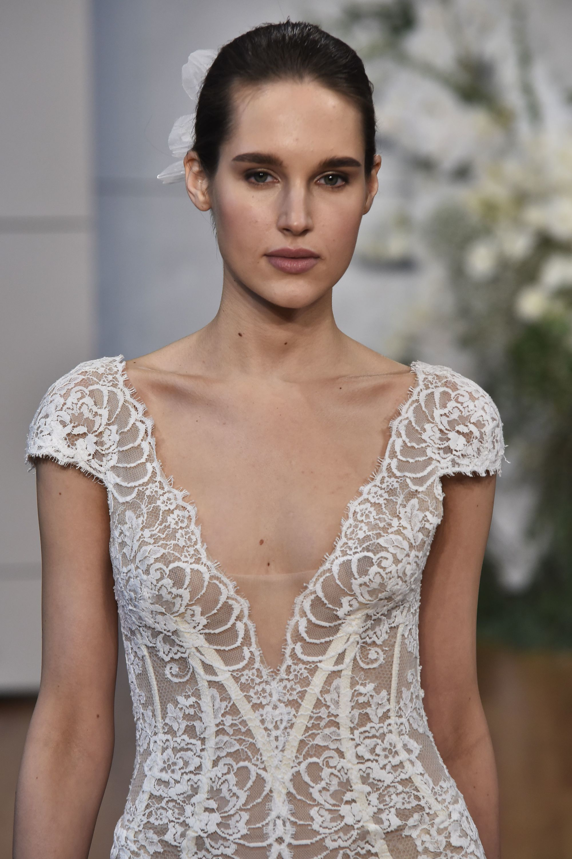 bridal updos: close up shot of model on the bridal runway with slicked back low bun, wearing v-cut wedding dress