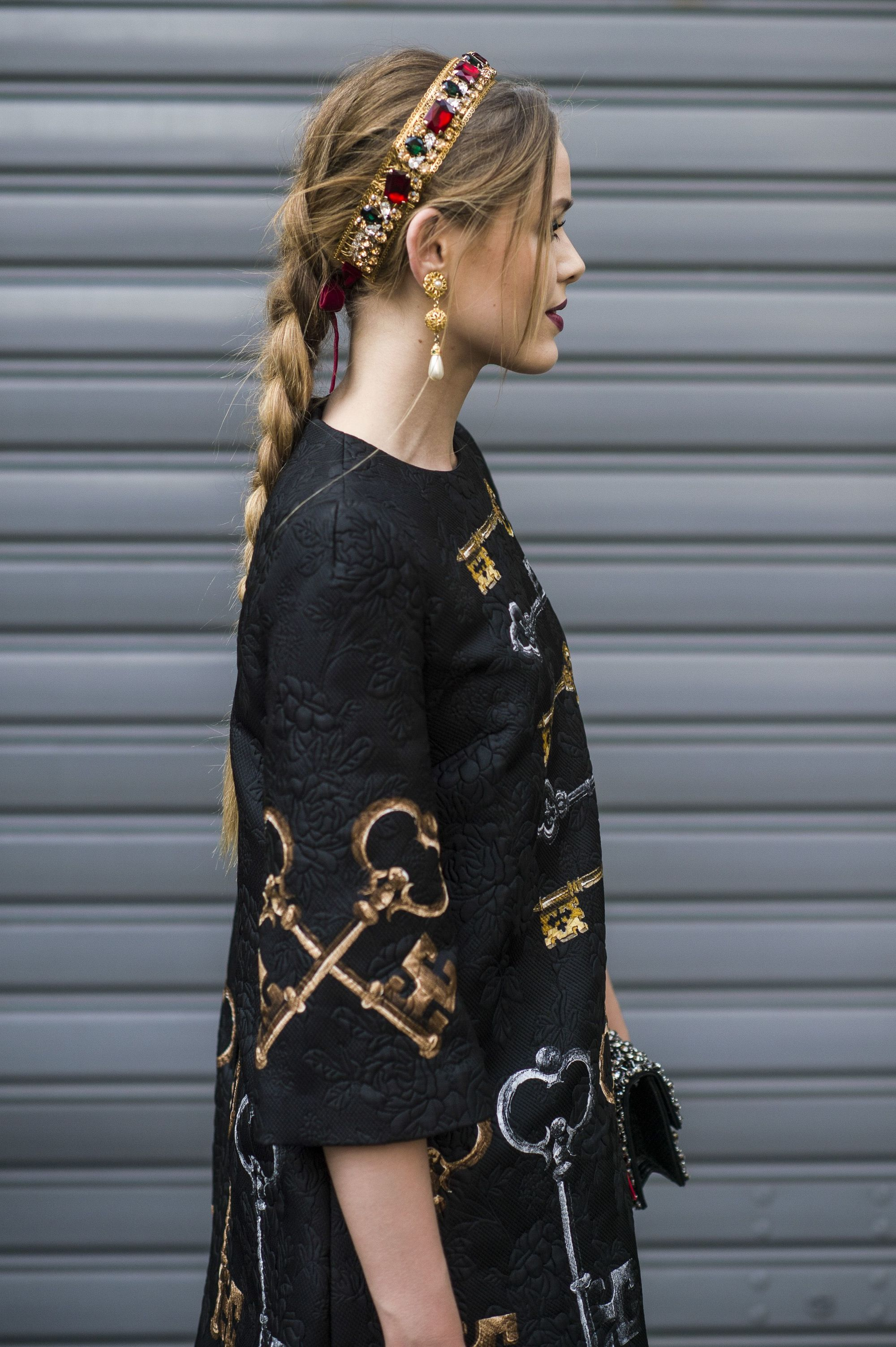 Side view of a woman with long golden light brown hair styled in a single braid, with a headband and black embroidered dress