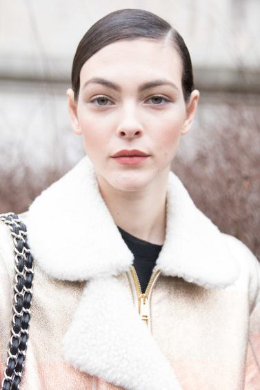 quick updos: close shot of woman with brown hair styled in side-parting smooth updo wearing a beige fluffy jacket